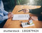 real estate agent holding house ... | Shutterstock . vector #1302879424