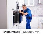 male technician wearing overall ...   Shutterstock . vector #1303093744