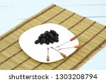 Small photo of Group of blackberries on a plate on a tablemate