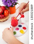 Child hands painting the easter eggs - closeup - stock photo