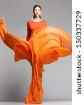 beautiful woman in long orange... | Shutterstock . vector #130337729