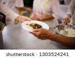 volunteers are giving food to... | Shutterstock . vector #1303524241