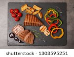 slate plate with grilled meat ...   Shutterstock . vector #1303595251