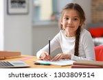 cute girl doing homework at home | Shutterstock . vector #1303809514