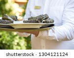 waiter carrying plates with... | Shutterstock . vector #1304121124