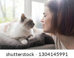 young woman petting her... | Shutterstock . vector #1304145991