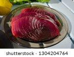 big tuna steaks on the plate... | Shutterstock . vector #1304204764