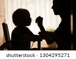 mother feeding baby toddler... | Shutterstock . vector #1304295271