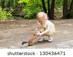 Kid Girl Feeds Squirrel In The...
