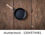 top view black pan on wood... | Shutterstock . vector #1304574481