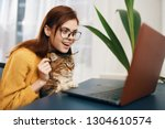 Stock photo woman glasses coffee with a confident happy look open laptop business cat yellow office sweater 1304610574