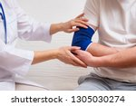 doctor helps the patient to use ... | Shutterstock . vector #1305030274