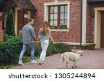 Stock photo successful young couple walking with a dog near home beautiful family moving to their new house 1305244894