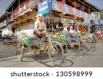 YANGON,MYANMAR  NOV.23; Ricksaws are a common transportation in asia on Nov.23, 2012 Myanmar.People can't effort there own transportation and religh on bicycle taxi's to go to places they want - stock photo