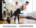 man exercise in gym with trainer | Shutterstock . vector #1305994504
