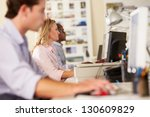 workers at desks in busy... | Shutterstock . vector #130609829