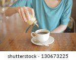 sugar pouring into a cup of tea | Shutterstock . vector #130673225