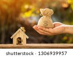 man hand hold money bag with... | Shutterstock . vector #1306939957