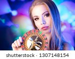 Casino concept. Portrait of young attractive woman, playing in casino. Poker chips, cards, roulette wheel, bokeh background. - stock photo