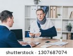 Small photo of middle aged worker in neck brace with broken arm sitting at table and talking to businessman in blue jacket in office, compensation concept