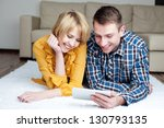 Young couple lying on the floor with digital tablet, smiling. - stock photo