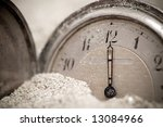 Small photo of Old pocket watch buried in sand. Lost time concept. Desaturated.