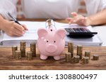 stacked coins and pink piggy... | Shutterstock . vector #1308800497
