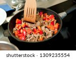 cook fries meat in a pan with...