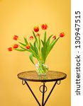 Red tulips in a vase on mosaic table. Vertical. - stock photo