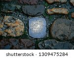 "Small photo of Basel, Switzerland - February 24, 2007: a piece of metal engraved in the pavement in the style of a stumbling stone with the writing ""here the love between Gabriele and Harald began to blossom (date)"""