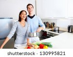 couple cooking healthy food in...