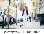 Stock photo a young redhaired caucasian woman walking along european street with small chihuahua breed dog of 1310481824