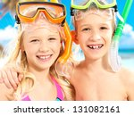 Closeup portrait of the happy brother with sister enjoying at beach.  Laughing children standing together in swimwear with swimming mask on head . - stock photo