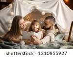 happy family reading book at... | Shutterstock . vector #1310855927