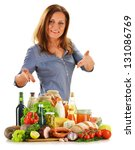 Young woman with variety of grocery products isolated on white - stock photo