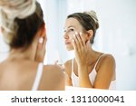 photo of woman applying face... | Shutterstock . vector #1311000041