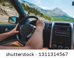 man driving car in mountains.... | Shutterstock . vector #1311314567