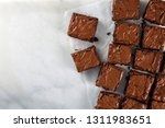 Chocolate brownie on paper on white marble top view flat lay looking down with text space on left copy space