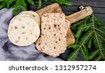 Small photo of Barley flatbread original Lapland bread on the wood cutting board. Finns call this bread name Rieska. Traditional food from north