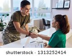 Young smiling army soldier meeting with his therapist and shaking hands while having a meeting at doctor