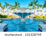 Luxury water fountain in tropical resort with palm trees. - stock photo