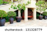 Tropical building  resort court yard with trees in the pots and bird cage. - stock photo
