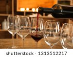 pouring of tasty red wine into... | Shutterstock . vector #1313512217