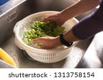woman washing vegetables in the ...   Shutterstock . vector #1313758154