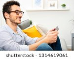 young man using tablet on sofa... | Shutterstock . vector #1314619061