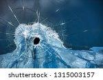 Small photo of gunshot hole through a pane of glass