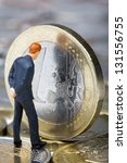 Figure of businessman looking on European Union on one euro coin. Euro crisis concept. - stock photo