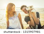 Stock photo loving couple having fun with their dog at the beach on vacation concept about people animals and 1315907981