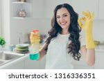 Small photo of Close up photo cheerful beautiful busy nice duties she her lady house hold okey symbol washing supplies pulverize promo wear jeans denim casual t-shirt covered by cute apron bright light kitchen