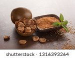 Small photo of Luo Han Guo aka Monk fruit natural herbal remedy and sugar on brown background. Powerful healthy sweetener.